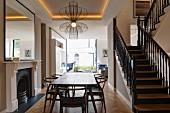 Elegant restaurierte Holztreppe mit schwarz lackiertem Geländer in offenem Wohnraum mit Kamin und modernem Panoramafenster