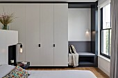 White fitted wardrobes in bedroom with custom, upholstered window seat