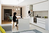 White, open-plan kitchen with island counter, dining area and daylight falling through skylight