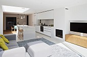 Open-plan interior with white, designer kitchen, fireplace, plasma screen, grey upholstered furniture and rug