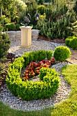 Angelegter Gartenplatz mit rot blühendem Begonienbeet, Buchshecke und Kunstwerk auf Sockel