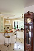 Antique, elegant long-case clock and open-plan, white, country-house kitchen with chandeliers