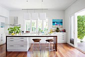 Kitchen island with white base cabinets and bar stools with rattan seat shells in a modern open kitchen