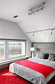 Schlafzimmer mit Dachschräge, rotem Teppichboden und gepolstertem Bettkopfteil