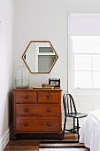 Vintage chest of drawers in front of polygonal mirror in corner of bedroom