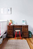 Wooden stool with red lacquered frame in front of solid wood desk next to cot