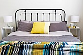 Double bed with black metal grid frame, gray bed linen, yellow cushions and brightly striped bedspread