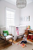Toddler on sisal rug in front of white crib and retro armchair next to window in corner of room