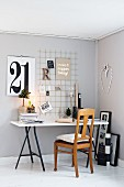 Desk below grid used as pinboard on grey wall