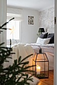 View into cosy bedroom with lit candle in floor lantern