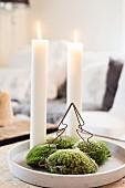 Zwei brennende Kerzen auf Tablett mit Moos und Metallbaum