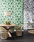 Round dining table with small wicker armchairs in front of wallpaper with green leaf motif, behind it is a black and white patterned wallpaper