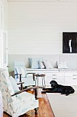 Wohnzimmerecke mit zwei Armlehnsesseln vor Sitzbank mit Schubladen, davor Hund auf Teppich