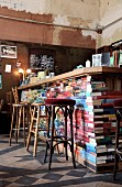 Various barstools at counter made from old books in shabby-chic interior of Café Hutmacher, Wuppertal, Germany