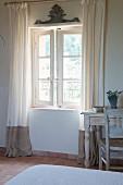 Bodenlange Vorhänge neben geöffnetem Sprossenfenster und Vintage Schreibtischplatz im Schlafzimmer