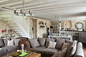 Gemütliche Eckcouch mit Kissen in grau-braunem Farbton, seitlich Treppenaufgang in offenem Wohnraum mit Küchenbereich im Hintergrund