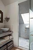 Concrete washstand counter with white countertop basin next to open glass door with view into shower area