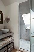 Betonierte Waschtischplatte mit weißem Aufsatzbecken neben offener Glastür und Blick in Duschbereich