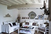 White sofa set with scatter cushions and antique armchair in living room with white wood-beamed ceiling