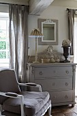 Antique armchair next to grey chest of drawers in vintage interior with French ambiance