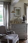 Antiker Sessel neben grauer Schubladenkommode in Vintage Ambiente mit französischem Flair
