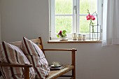 Cushions and cup of tea on wooden bench below window