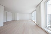 Spacious, empty room in apartment with laminate floor, white walls & floor-to-ceiling windows