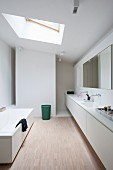 Floating washstand with twin sinks, shower area, skylight and white bathrub