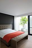 Elegantes Doppelbett an schwarzer Wand mit taupefarbenem Kopfteil und passender Kleiderbank, Blick durch offene Schiebetür in Patio mit Kübelpflanze