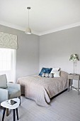 Blanket and scatter cushions on double bed against pastel-grey wall in corner of bedroom