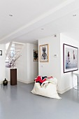 Modern interior with grey epoxy resin floor, white beanbag against wall and framed pictures