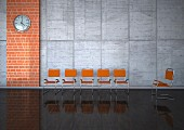 Waiting room with glossy floor, orange chairs & wall clock