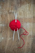 Ball of red wool with knitting needles on wooden surface (top view)
