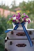 Romantic flower arrangement with blue striped ribbon and elegant brooch on stacked vintage suitcases