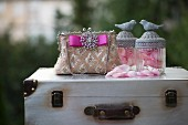 Elegant, sequinned handbag with brooch and pink ribbon and glass jars of rose petals with bird figurines on lids on top of vintage suitcase