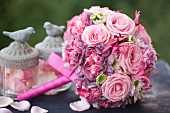 Romantischer Hochzeitsstrauß mit rosafarbenen Rosen und Glasgefäßen mit Vogelfiguren gefüllt mit Rosenblütenblättern