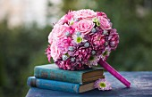 Romantic, pink bridal bouquet arranged with blue, antiquarian books