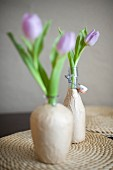 Upcycling: vases made from glass bottles covered with brown paper