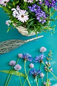 Basket of Cape daisies & purple lantana next to cornflowers, sage & chive flowers