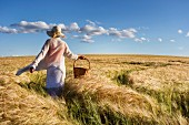 Woman wearing straw hat and carrying basket walking through summer cornfield