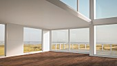 Empty holiday home with glass walls amongst sand dunes on North Sea beach