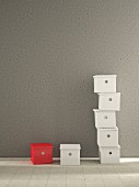 One red and multiple white storage boxes against grey concrete wall