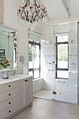 Pale grey bathroom washstand below elegant mirror, chandelier and modern shower area with glass partition