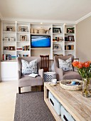 Comfortable living room with white fitted shelving, TV and beige armchairs