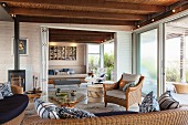Comfortable lounge area with wicker furniture, round glass table and log-burning stove; view of terrace