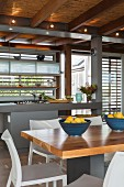 Modern fitted kitchen with island counter, dining table and reed ceiling with wood-beam structure