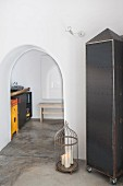 Cupboard made from riveted metal panels and candles in birdcage next to arched doorway leading into kitchen