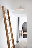 Old wooden ladder leaning against white wall for use as a clothes rack in bedroom