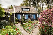 Wooden house with blue shutters and terrace amongst flowering beds in garden