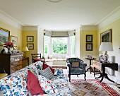 Sofa mit blumigem Stoffbezug und passende Kissen, Polstersessel und klappbarer Antiktisch in gelb getöntem Wohnzimmer mit Erker